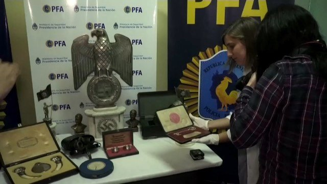 Interpol investigators display a number of items that are among the seized Nazi artifacts (Photo//AP)